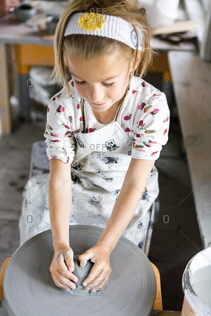 Blonde girl forming pottery on wheel