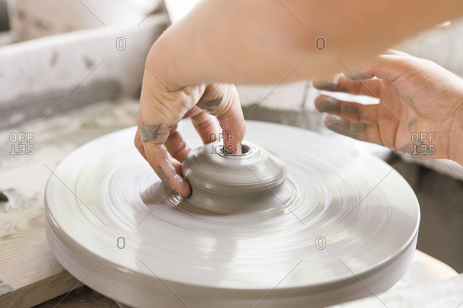 Child forming pottery on wheel