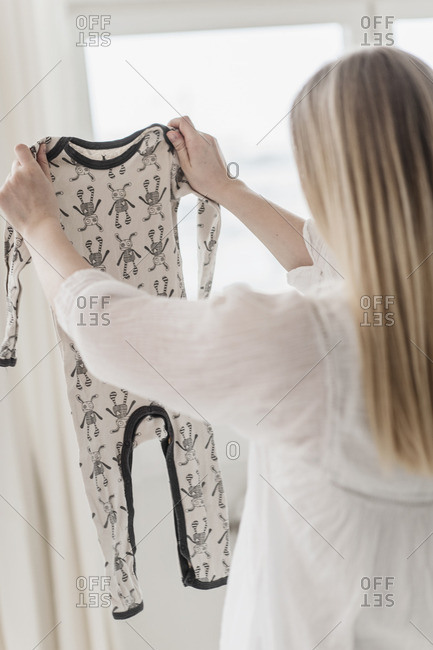 Woman inspecting onesie for quality