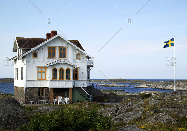 Wooden house on rocky coast flying Swedish flag