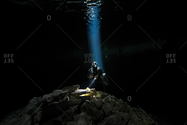 Scuba diver illuminated by rays of light while diving in Yucatan Peninsula, Mexico
