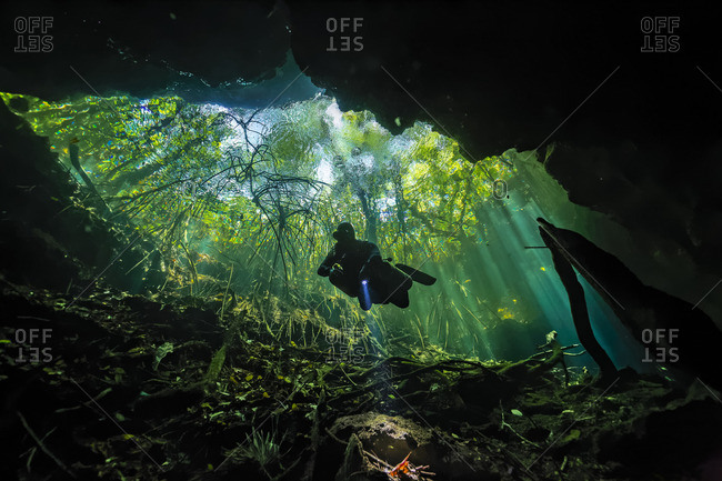 Scuba diver explores an underwater cave in the Yucatan Peninsula, Mexico