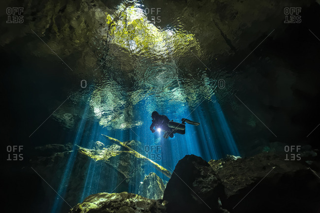Scuba diver exploring an underwater cave in the Yucatan Peninsula, Mexico