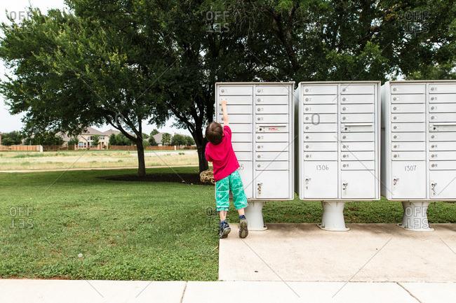 Boy checking outdoor mailbox