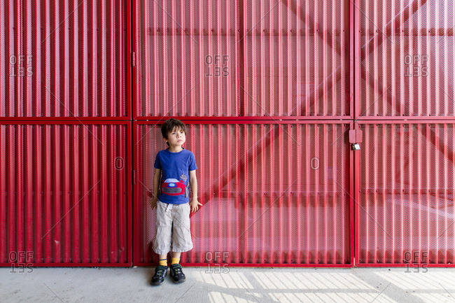 Boy standing by metal gate