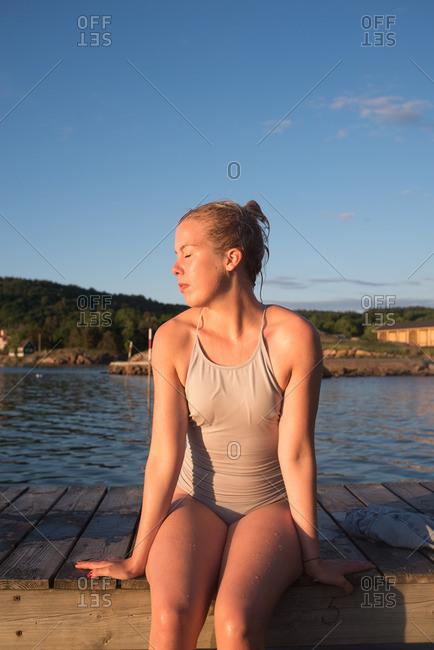Woman basking in sun on dock