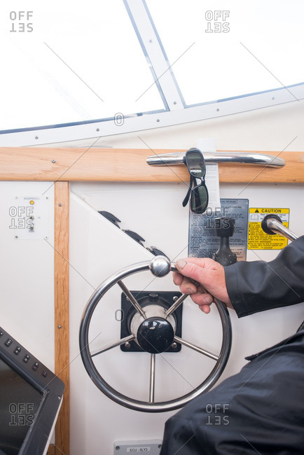 Captain with hand on a boat's steering wheel