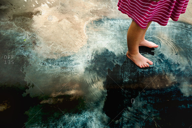 Girl's feet on reflective puddle