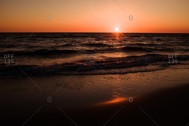 Waves breaking on a sandy beach as the sun is setting
