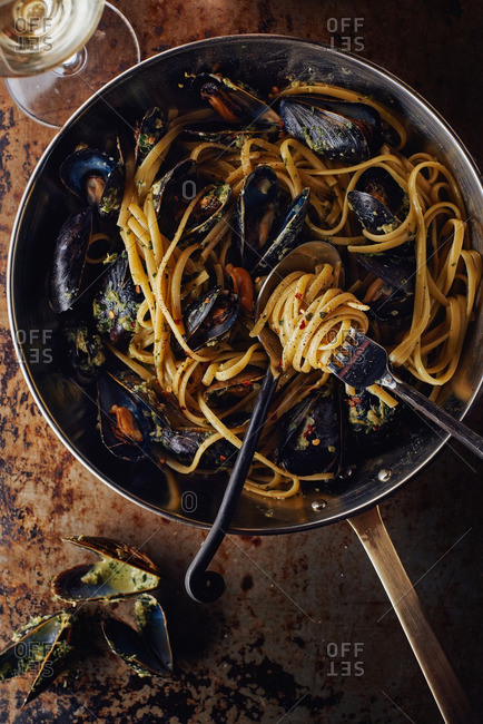Overhead view of linguine and mussels in skillet