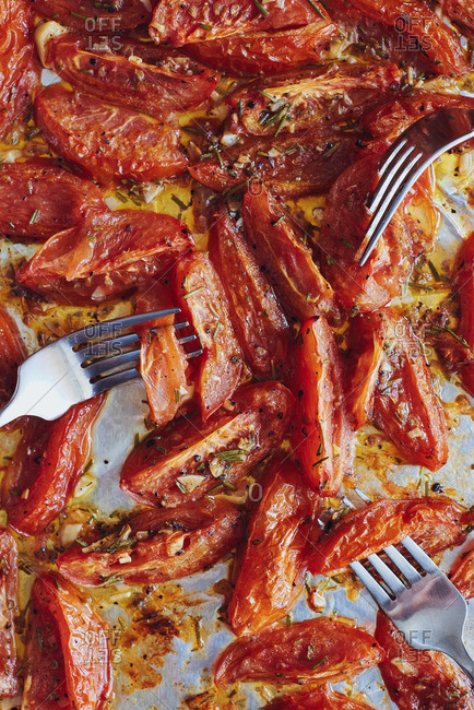 Roasted tomatoes on pan with forks