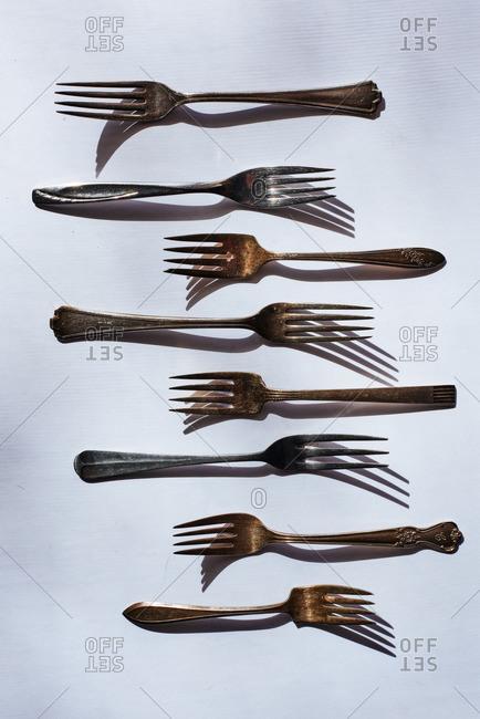 Arrangement of vintage tarnished forks on white background