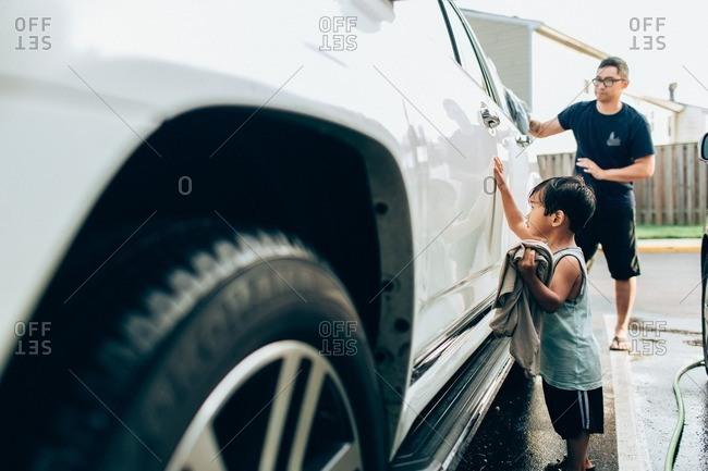 Asian toddler helping his dad wash a car