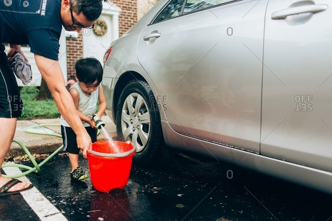 Asian toddler filling bucket with water to help his dad wash car