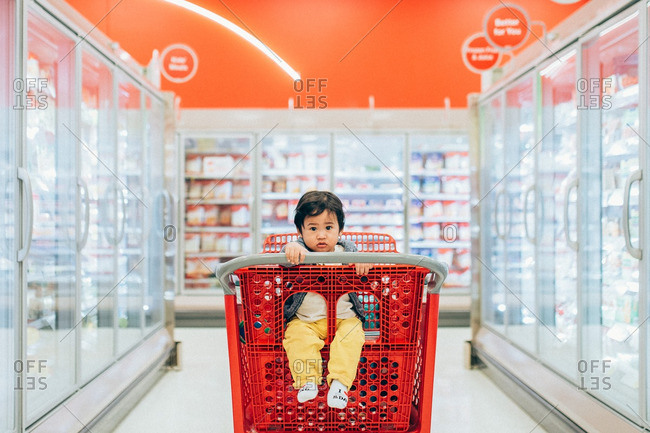 Asian baby sitting in a red shopping cart