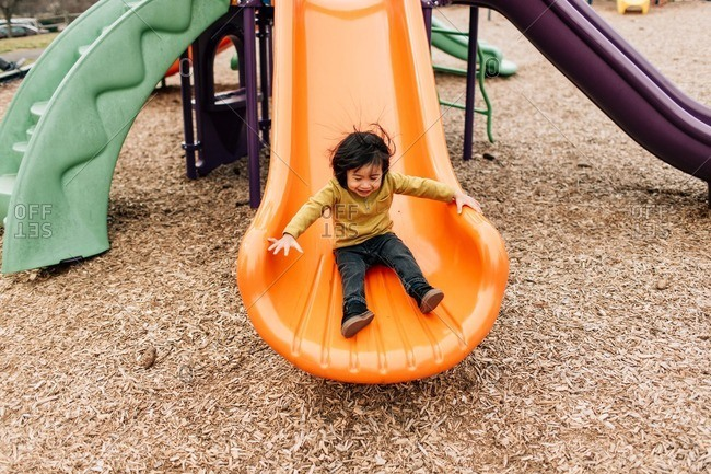 Asian toddler boy sliding down orange slide