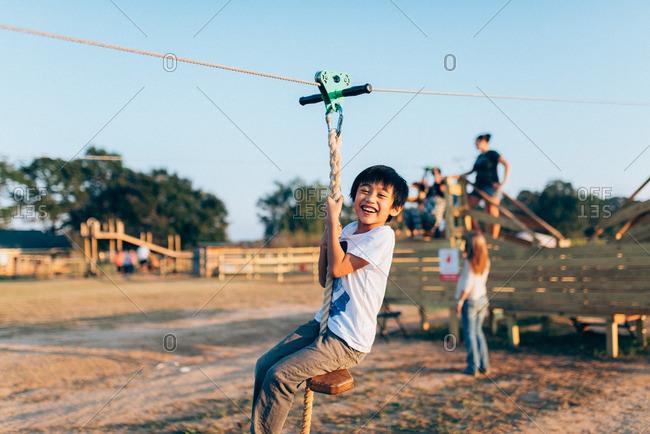 Asian boy riding on a zip line