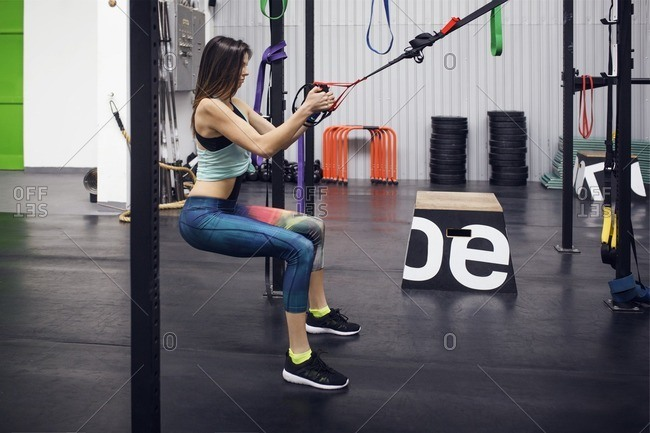 Side view of determined female athlete pulling suspension belts at gym