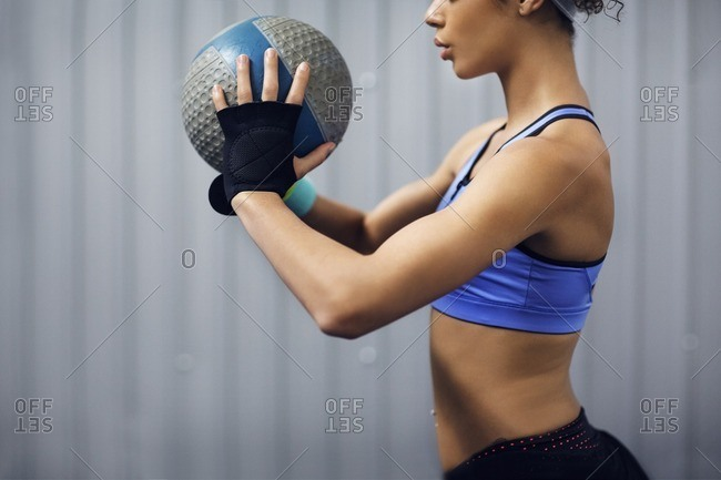 Midsection of female athlete exercising with medicine ball in gym