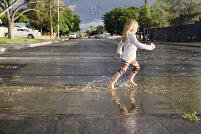 Side view of girl running on wet street during rainy season