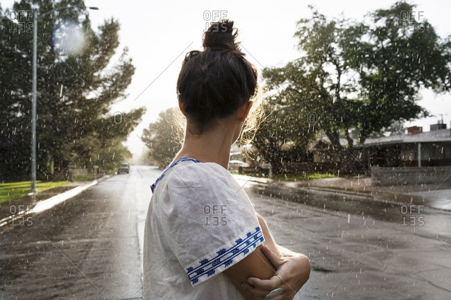 Side view of woman standing arms crossed on road during rainy season