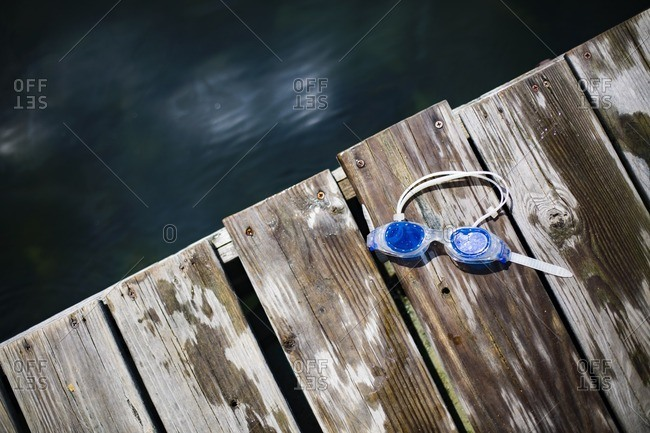 Overhead view of swimming goggles on boardwalk by lake