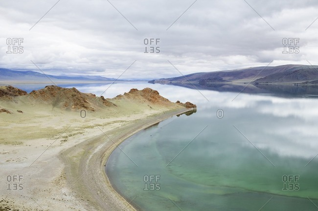 Scenic view of calm lake and mountains against cloudy sky