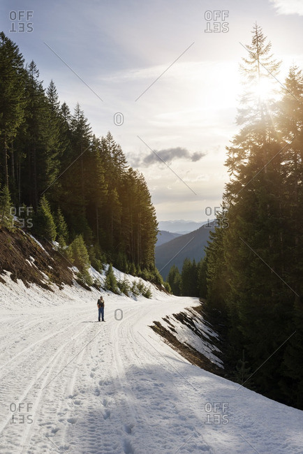 Mid distance of man standing on snow covered footpath on mountain at Gifford Pinchot National Forest