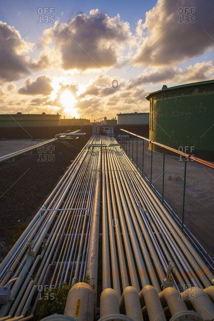 Saint Croix, U.S. Virgin Islands,  - November 30, 2013: Pipelines at industry against cloudy sky during sunset