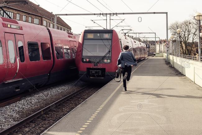 Rear view of businessman running on railroad station platform