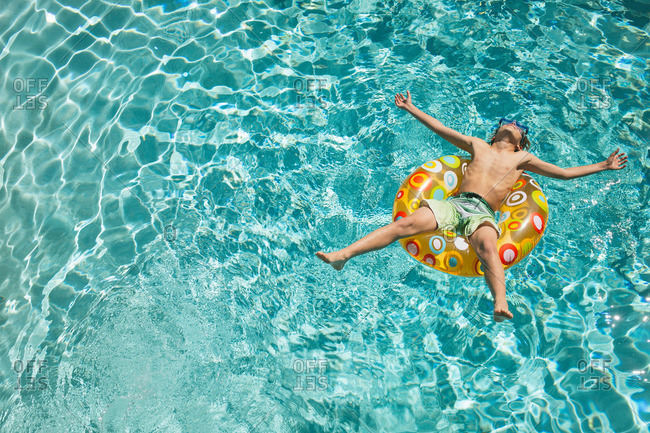Child floating in colorful inflatable ring in a pool