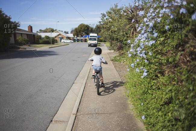 Child riding a bicycle along a suburban sidewalk