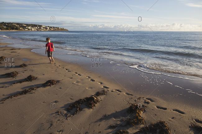 Boy walking along a beach alone