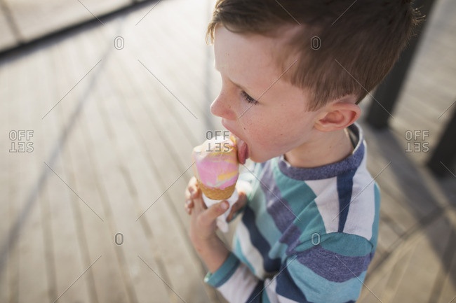Boy licking an ice cream cone on a beach boardwalk