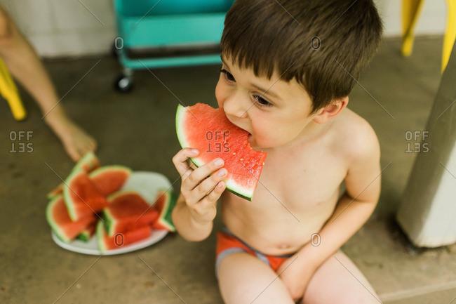 Boy in underwear eating watermelon