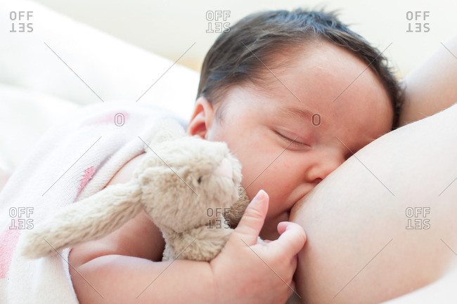Mother breast feeding newborn baby girl