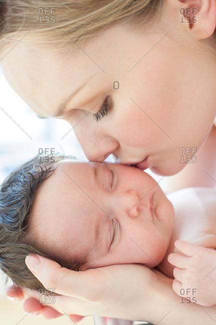 Mother kissing newborn baby girl