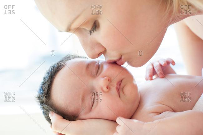 Mother kissing newborn baby
