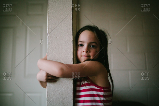 Portrait of a girl hugging a post