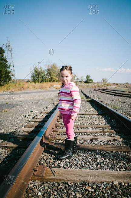 Girl wearing a striped sweater and boots standing on a railroad track