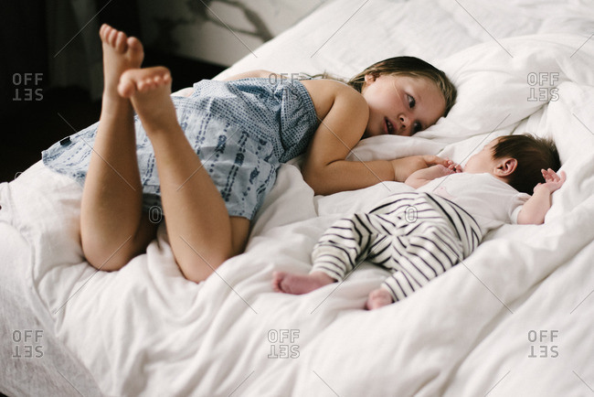 Girl watching sleeping newborn