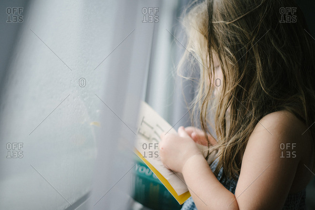 Girl at window reading