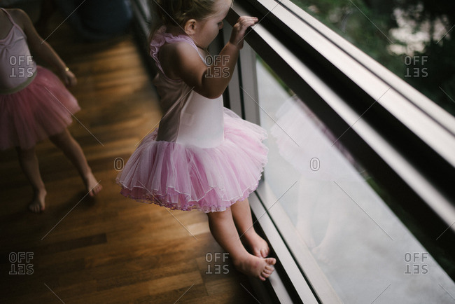 Girl in tutu climbing window