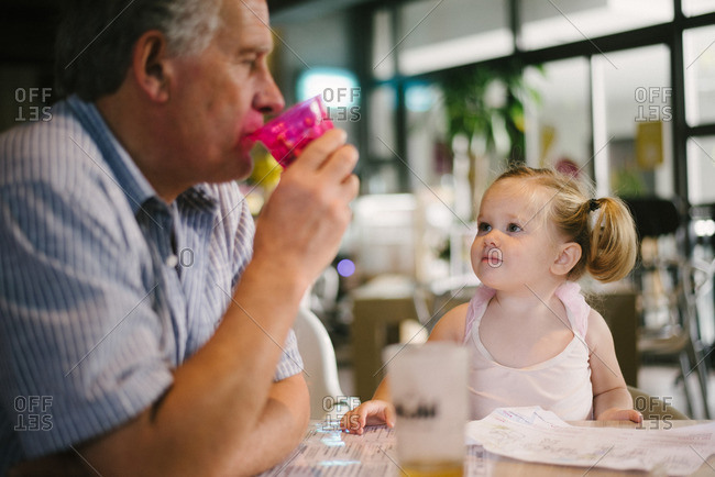 Girl watching man drink from cup