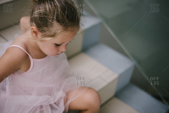 Girl in tutu resting on steps