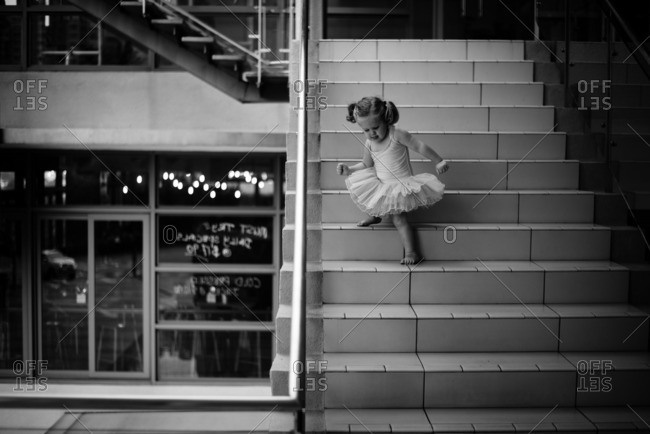 Girl in tutu doing down steps