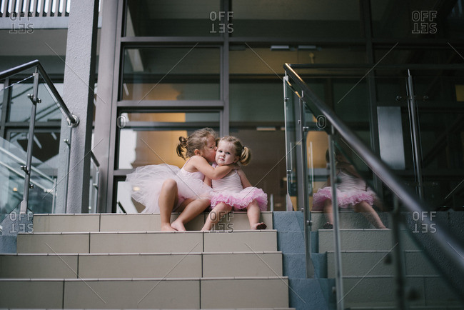 Girl hugging another in tutu