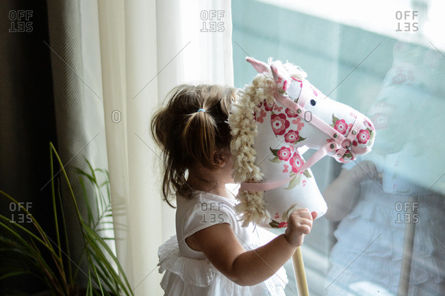 Girl with stick horse at window
