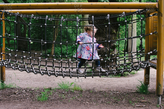 Girl on playground rope bridge