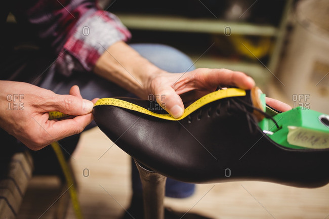 Close up of cobbler measuring a shoe with a tape